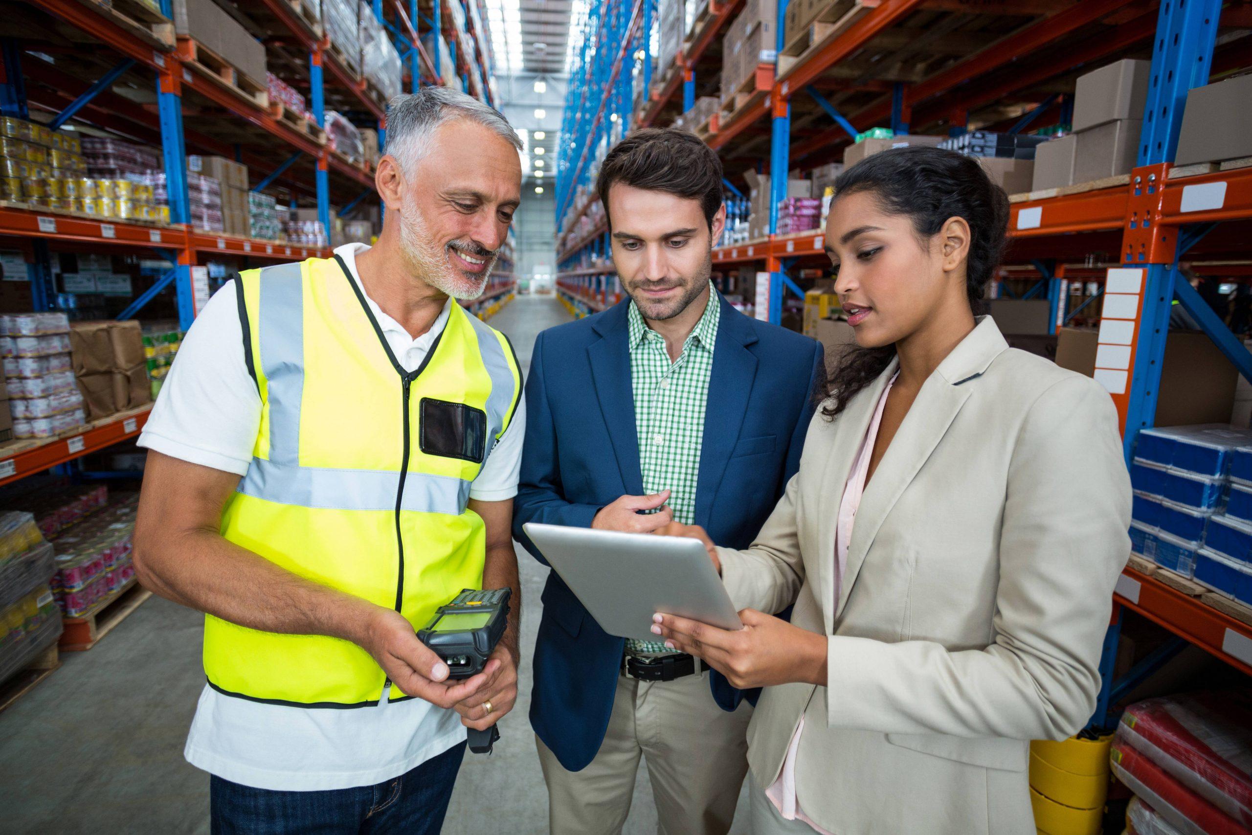 trois personnes qui regardent une tablette dans un entrepôt de marchandises