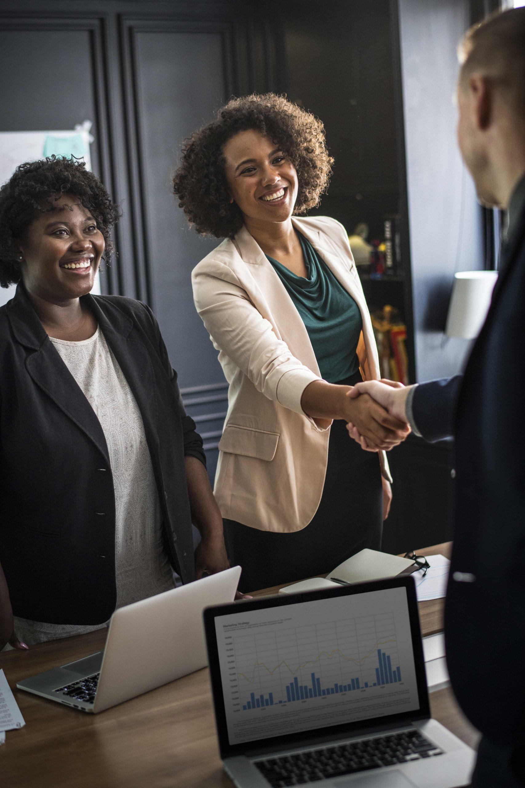 deux femmes qui serrent les mains avec un homme dans le bureau