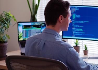 un développeur devant deux ordinateurs