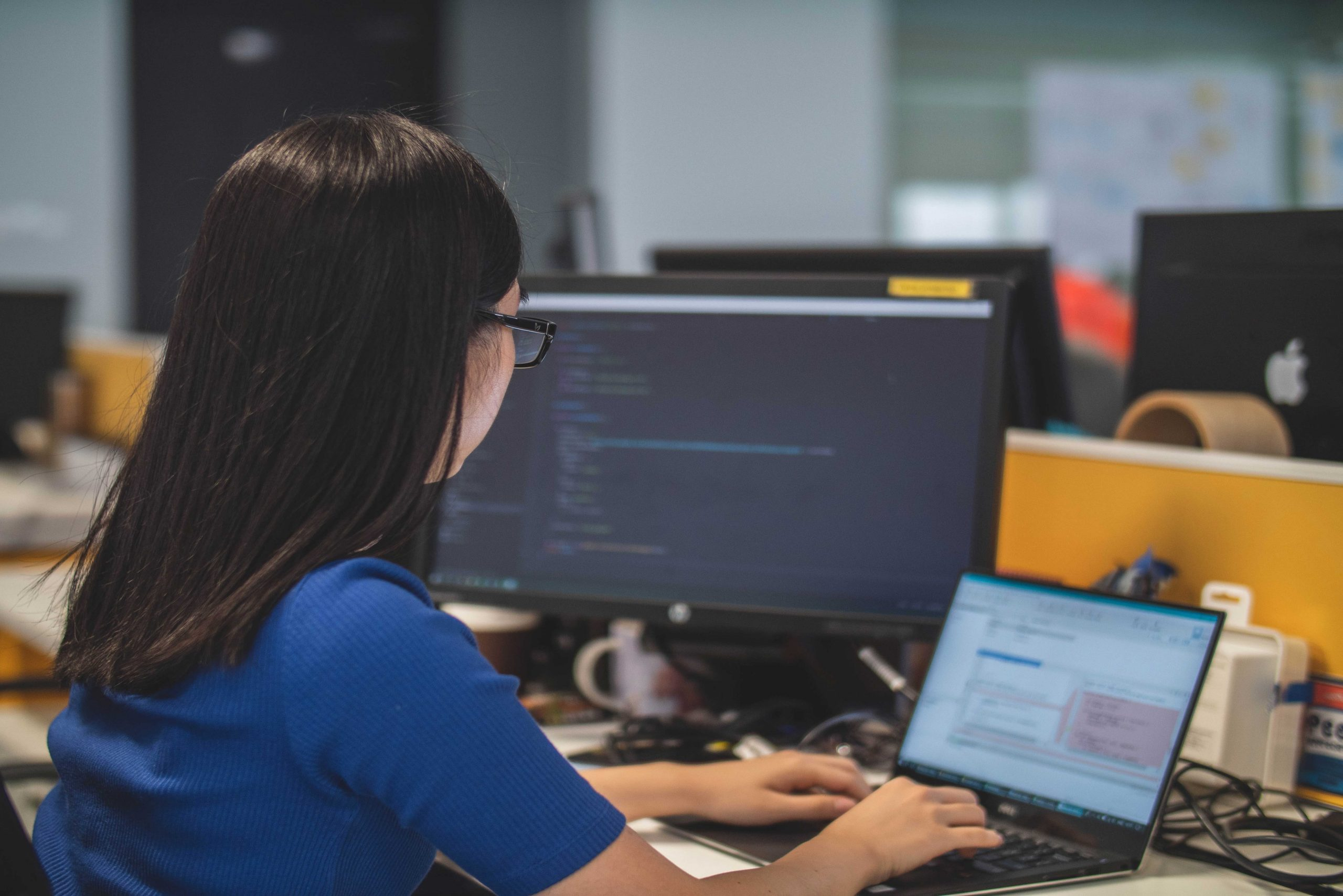 une développeuse au bureau devant deux ordinateurs
