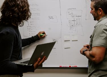 deux peronnes qui écrivent sur un tableau